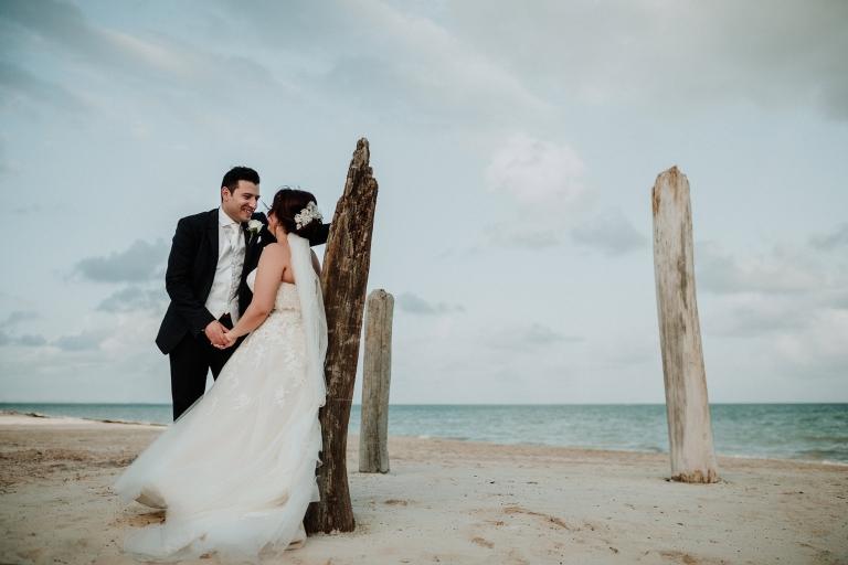 Groom holds bride's hand on beach by the ocean.